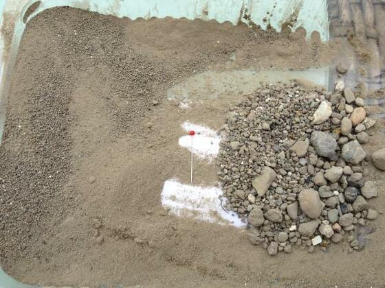 Bohrgut mit einem Küchensieb ausgesiebtin der mitte eine Stecknadel als vergleich.. Es ist mehr sand wie Stein.